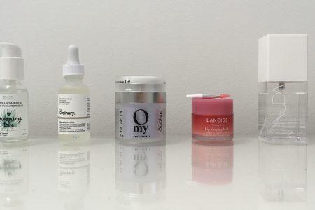 5 produits de soins du visage et leur reflet, sur fond blanc.