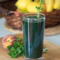 чаша пълна със зелено смути с маточина и спирулина