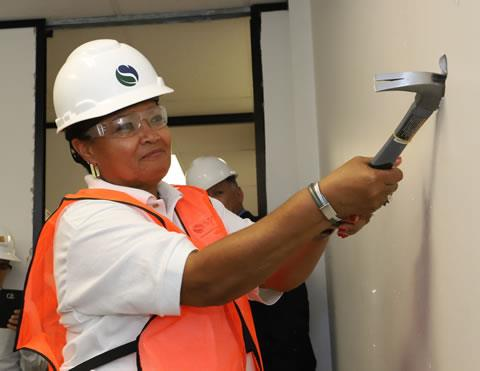 Spring ISD Board President Rhonda Newhouse takes an honorary first swing at demolishing a wall to create a larger dispatch center at the future Spring ISD Police Command Center