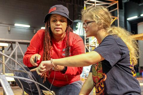 Westfield High School Director of Theatre Monet Salone discusses puppet construction details with sophomore Lily Terflinger on the set of 'Little Shop of Horrors'