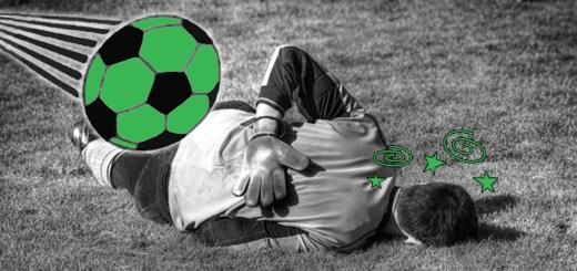 Fußballer liegt am Boden und ein Ball rast auf ihn zu