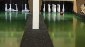 Bild einer Kegelbahn, auf der eine Kugel auf die neun (noch) stehenden Kegel zurollt. Auf der Nebenbahn sind bereits einige Kegel gefallen.