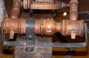 """Muffler strap"" tension mechanism"