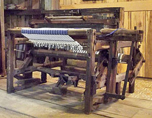 Rocker-beater loom with fly shuttle mechanism. Front view.