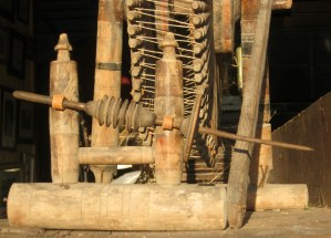 An iron spindle attached to the maidens at an angle. Note the hemp thread to form the cross bindings between the sets of spokes on the drive wheel to support the drive band.