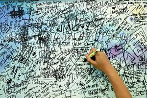 A man writes messages and well-wishes for family members of passengers onboard the missing Malaysia  ?