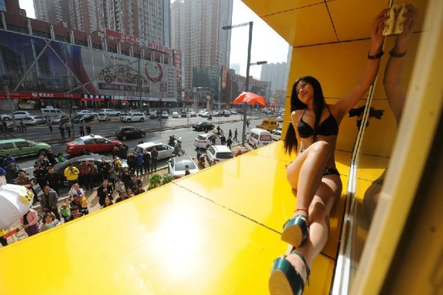 One of the bikini wearing cleaners poses above the shop in Taiyuan, the capital of North China's Shanxi province