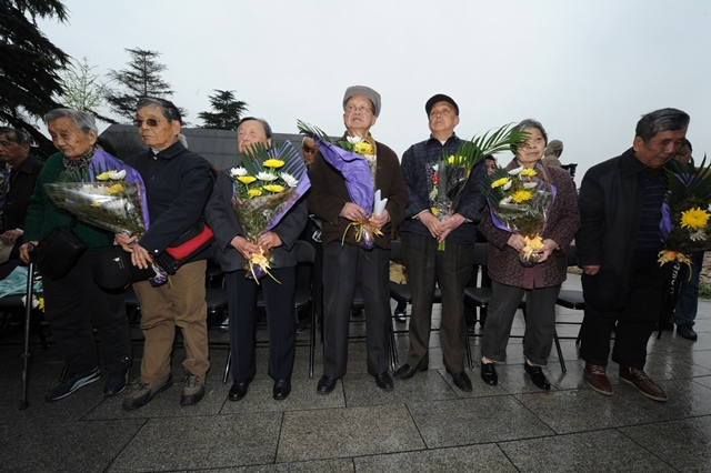 Survivors and relatives of victims of Nanjing Massacre take part in a ceremony to mourn the Nanjing Massacre victims in front of a wall inscribed the name list of victims at the Memorial Hall of the Victims in Nanjing Massacre by Japanese Invaders  on the Qingming Festival in Nanjing, capital of east China's Jiangsu Province, April 5, 2015. Japanese troops captured Nanjing, then China's capital, on Dec. 13 of 1937 and started a 40-odd-day slaughter. More than 300,000 Chinese soldiers who had laid down their arms and civilians were murdered, and over 20,000 women were raped. (Xinhua/Han Yuqing) (lfj)