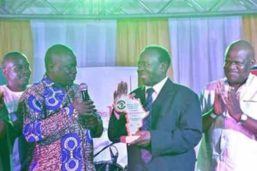 Sembuule (c) recieves his award from Fort Portal MP and PAP patron Alex Ruhunda