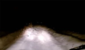 The car is seen travelling down a snowy road