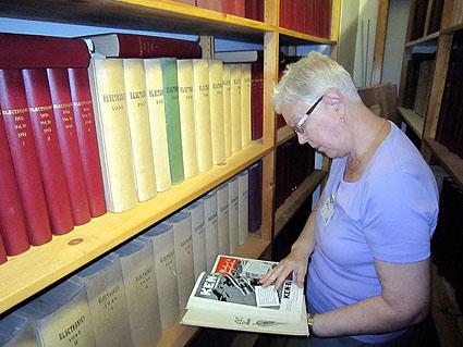 Ritva, OH2CJ, tutkii arkiston hyllyjä.