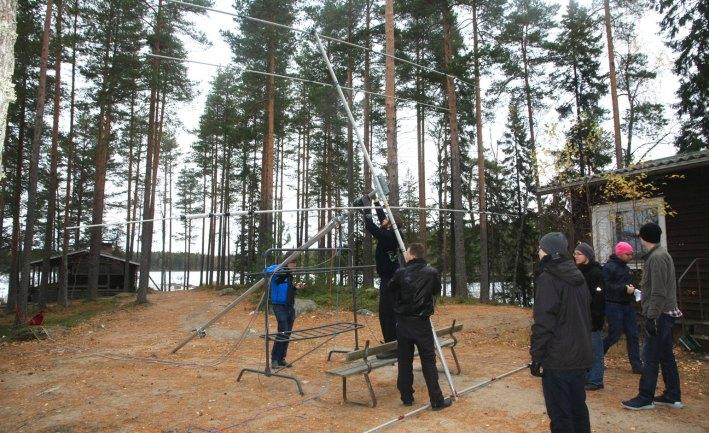 Leirin osallistujat nostavat pikkumastoa, jonka päässä on yagi-antenni.