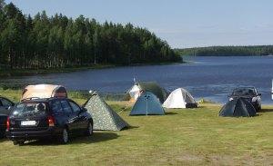 Telttoja järven rannalla.
