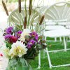 White fan back folding chair in use with flowers