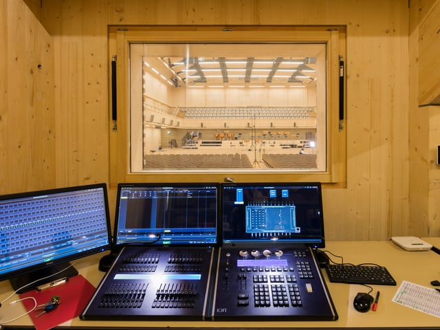 Two screens and a control panel are in a small room from which you can see the sound hall.