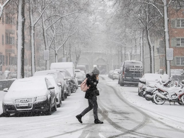 Woman crosses a snow-covered street in Zurich.