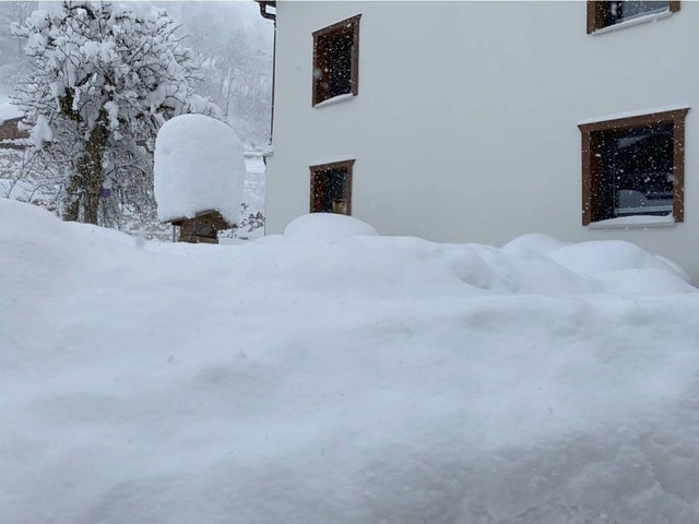 Mountains of snow in front of a wall of houses.