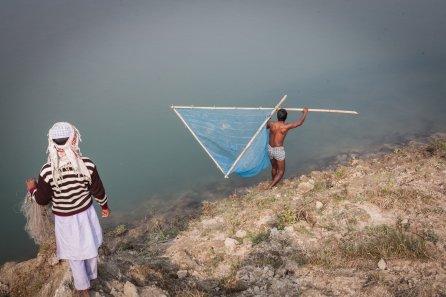 Mohammed Ghiasuddin goes fishing in the Guruphela near Kurashakati, Kokrajhar, Assam while his son watches on.