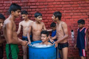 A judoka takes 'ice bath' in a drum filled with ice and water as others wait for their turn at the end of their day's practice at the Judo Traini ng Center in Gurdaspur, Punjab, India. August 04, 2016.