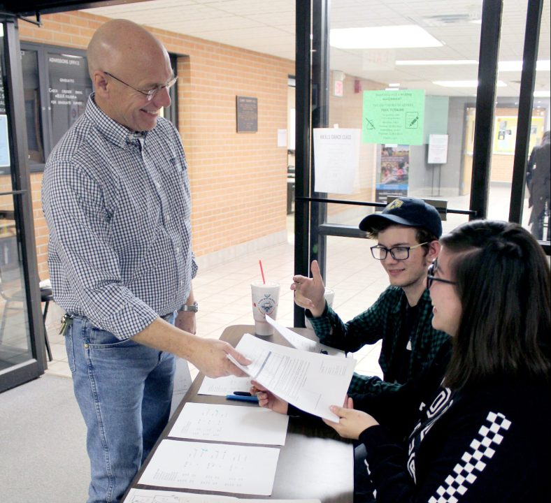 SSC Liberal Arts and Humanities Vice Chair John Bolander (left) hands off a ballot to a team of volunteers during the inaugural Trojan Speech and Debate Tournament last week.