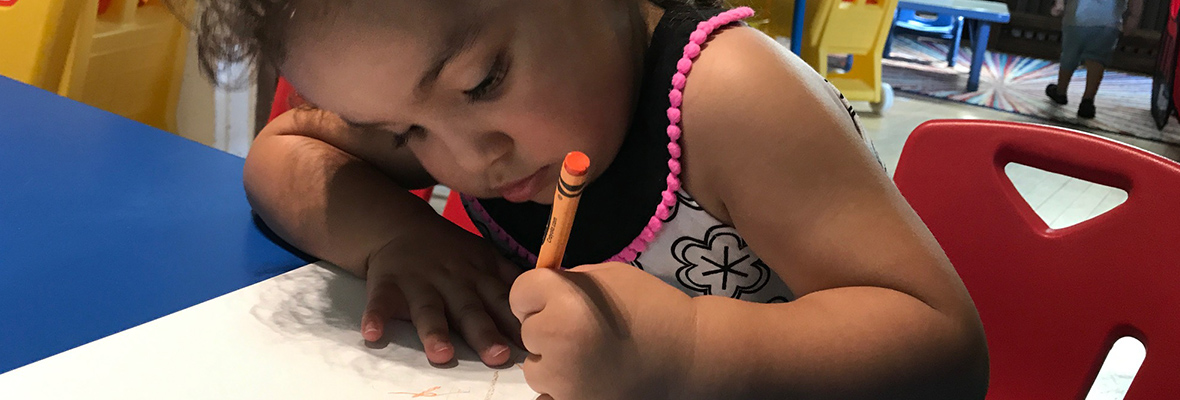 child drawing with a crayon