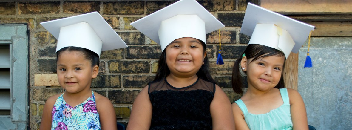 Three smiling young girls in white graduation caps