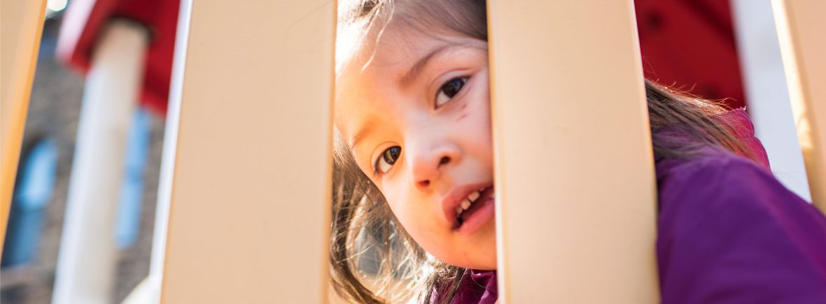 Young girl looking through slats on a playground