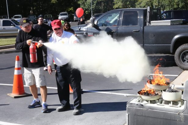 Ray Pensy of Brinklow practices using a fire extinguisher under the watchful eye of Fire Chief Emeritus George Brown during the the Sandy Spring Volunteer Fire Department Open House held at Station 4 on Brooke Road last Sunday afternoon (10/1/17).