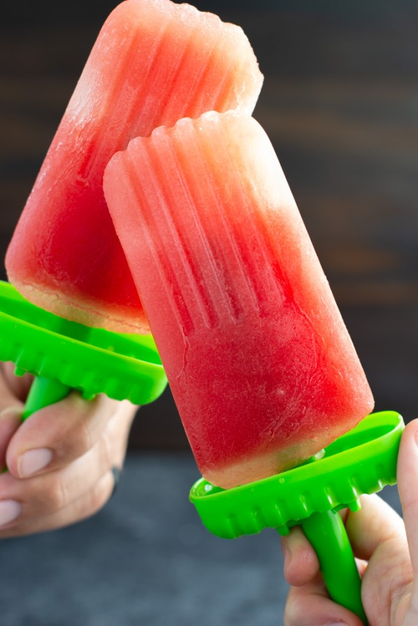 Two hands holding two homemade watermelon popsicles with green bases.