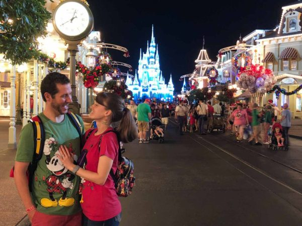 A happy couple posing on Main Street USA in front of Cinderella Castle at the Disney Christmas Party.