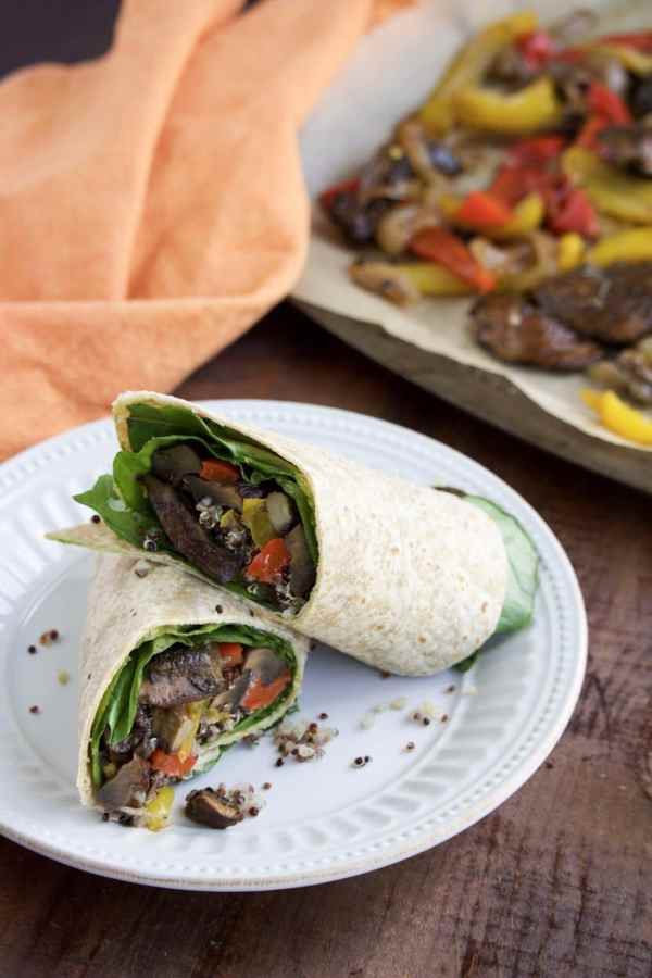 Two veggie hummus wraps resting on each other on top of a white textured plate that's sitting on a rustic background.
