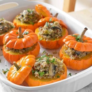A large white casserole dish filled with 6 mini stuffed pumpkins.
