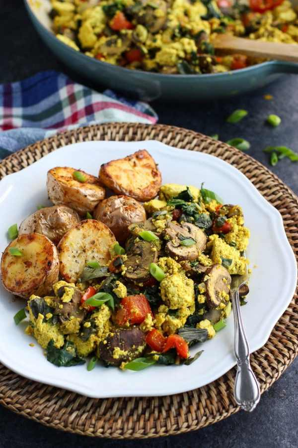 Low-carb vegan curried tofu scramble with vegetables on a white plate with a textured background.
