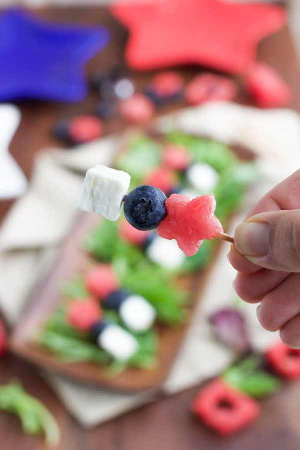 A hand holding a small skewer of a star-shaped piece of watermelon, one blueberry, and a small piece of vegan feta cheese.