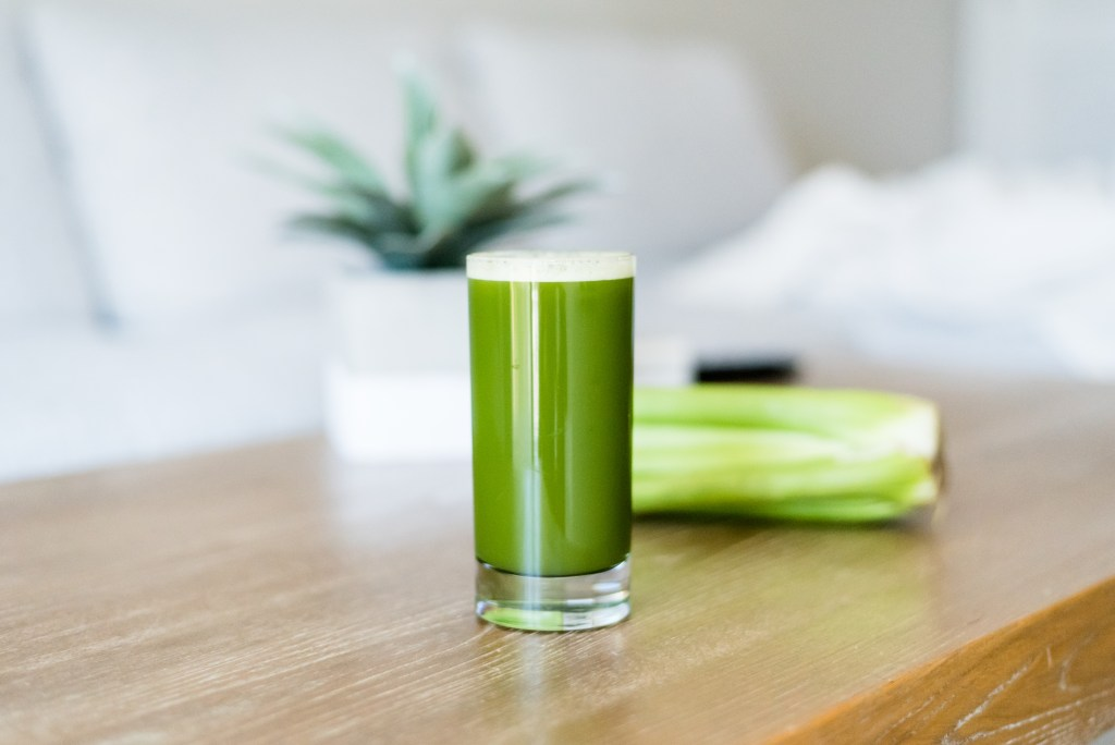 celery juice in a glass on a coffee table with a celery stalk behind it