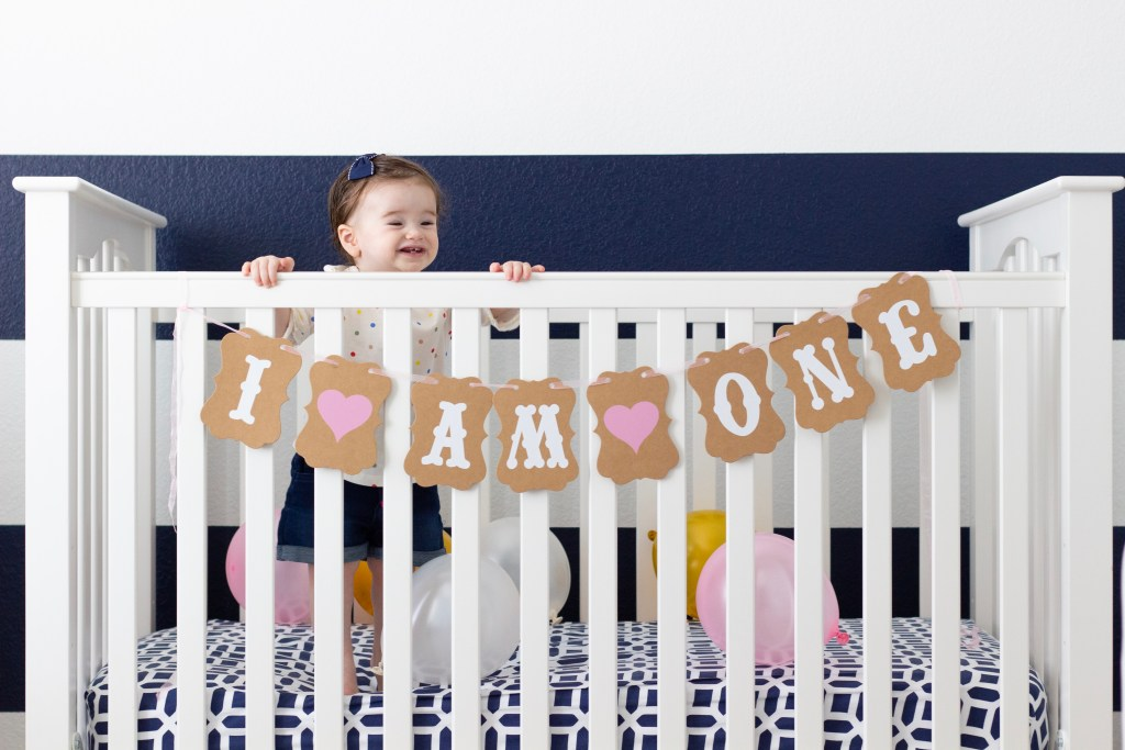 Baby in a crib with a navy and white striped wall behind her