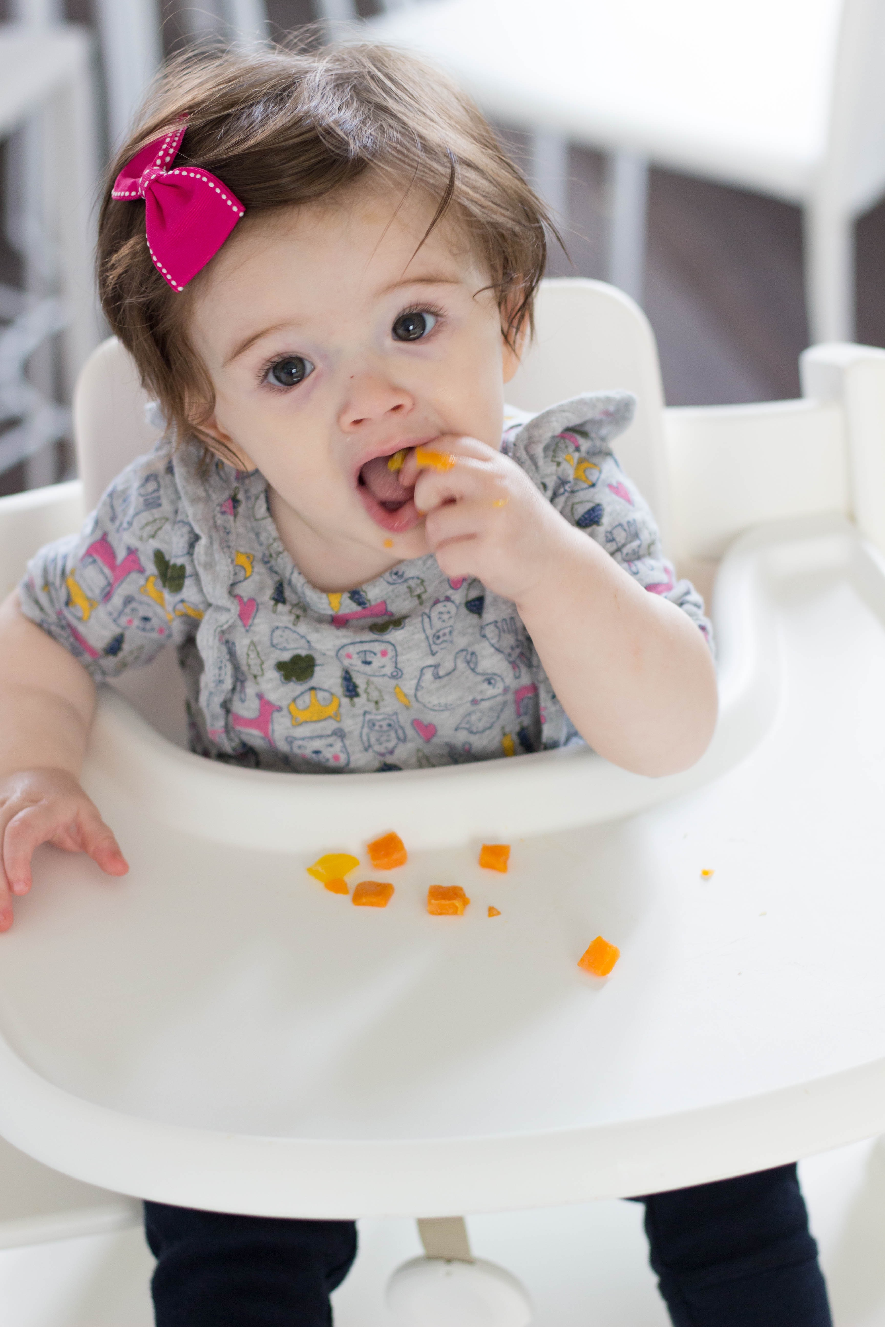 Baby eating food in a high chair