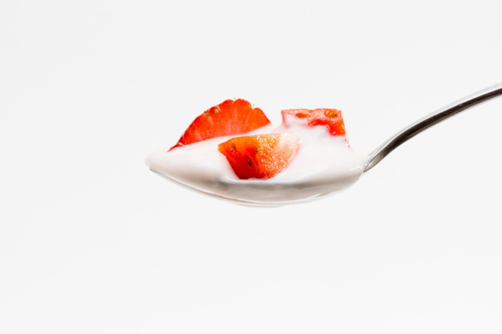 Yogurt on a spoon with strawberries