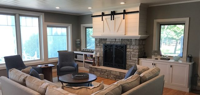 Renovated Lake house interior design_mindful gray_blue_shiplap and fieldstone fireplace_barn door hides TV
