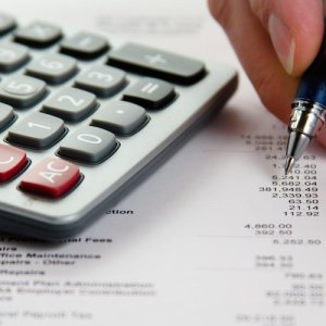 A calculator and detailed receipt are used in financial planning.