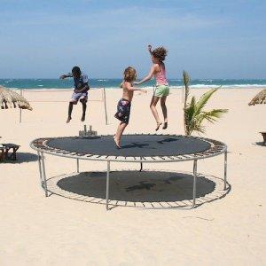 Three children jumping on a trampoline set up on a sandy beach.