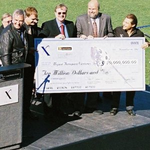 An oversize check for ten million dollars is presented at an outdoor charity event.