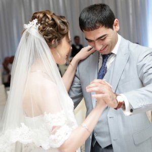 A bride and groom dancing. The woman faces away from the camera, looking at the man. His eyes are fixed on his footsteps.
