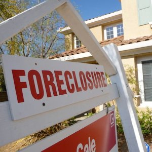 """A white and red """"Foreclosure"""" sign in front of a house."""