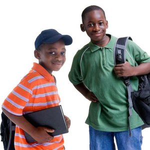 Two children smile with books and backpacks in tow, ready to head to school.