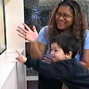 A child therapist encourages her patient, a young boy pointing excitedly at a diagram.