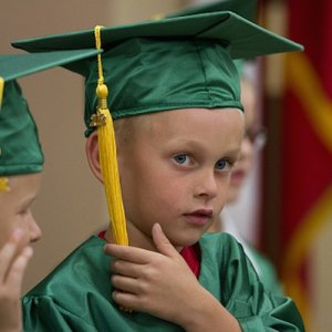A young boy in a green cap and gown at his kindergarten graduation.