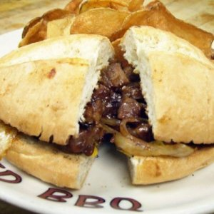 A juicy beef brisket sandwich plated with barbecue potato chips.