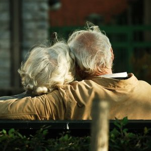 An elderly couple sit on a bench, the back of their heads visible, leaning into each other.