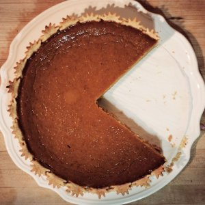 Pumpkin pie on a decorative white plate, a generous slice already taken from the delicious dessert.